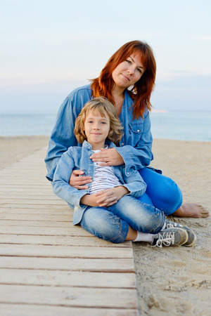 mother and daughter resting near the sea - focus on the mother photo