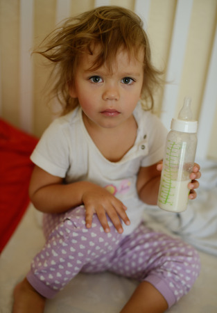 toddler girl with bottle of milk in bed photo