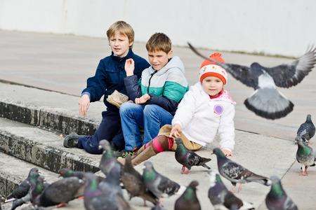three children feeding doves in the city photo