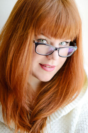 portrait of caucasian redhead girl with glasses photo