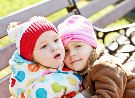 two toddler friends hugging outdoors photo