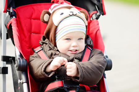 baby stroller: happy baby boy in red stroller Stock Photo