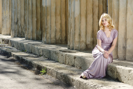 beautiful young model sitting near old columns photo