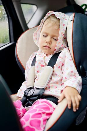 toddler girl sleeping in car seat photo