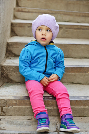 cute toddler girl sitting on the stairs photo