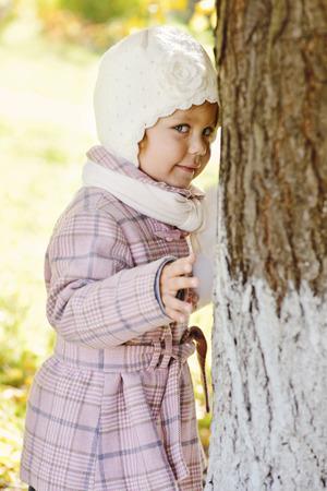 shy toddler girl near the tree photo