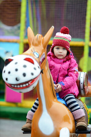 toddler girl  in theme park  on the horse photo