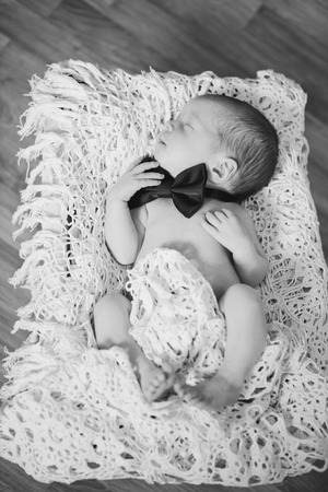 newborn boy wearing bow tie in black and white photo