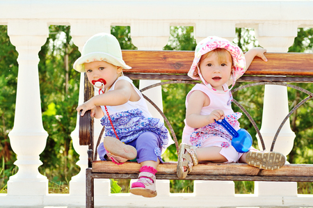 baby friends sitting on the bench photo