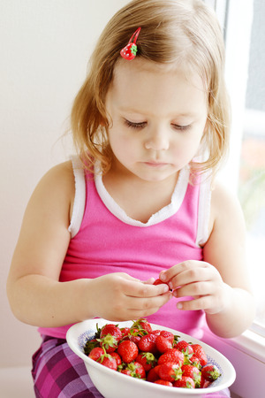 toddler girl eating strawberry near the window photo