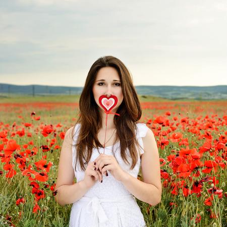girl with heart in poppy field photo