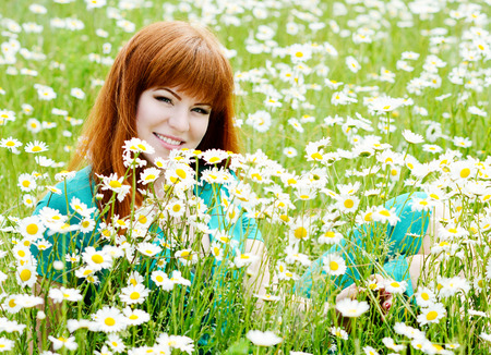 ginger girl in the field of daisy photo