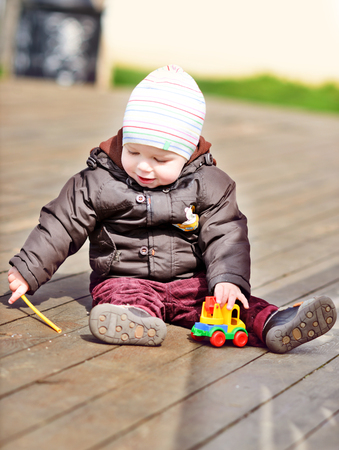 toddler boy  playing with toy outdoors   photo