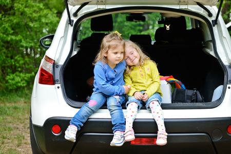 two little friends girls having fun in the car photo