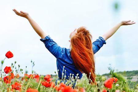 redhead girl in field is enjoying sun photo