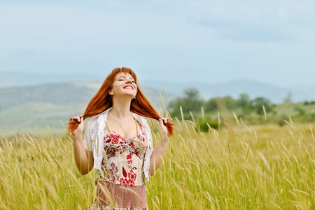 redhead girl in field enjoying sun photo