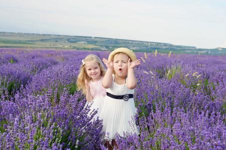 peek a boo: two girls having fun in lavender field