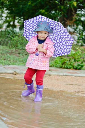 Adorable toddler girl at rainy day in summer photo