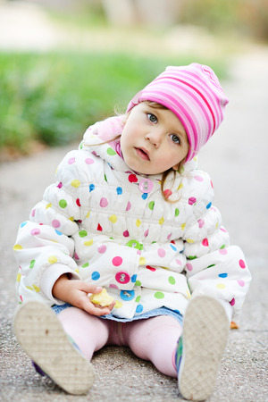 sitting on the ground: toddler girl sitting on the ground outdoors Stock Photo