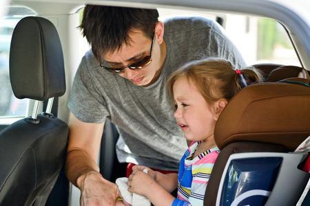 restraint: father  fastening  crying  daughter   in car Stock Photo
