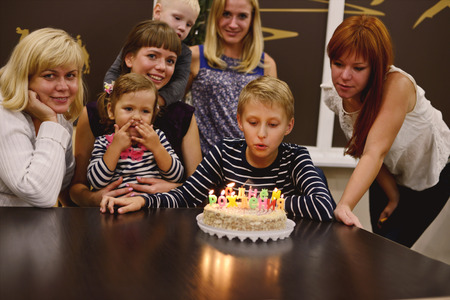 boy and his family in his birthday in light of candles photo