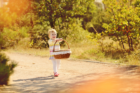 baby girl running  with basket in fall park photo