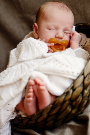 a lovely sleeping little newborn with dummy photo