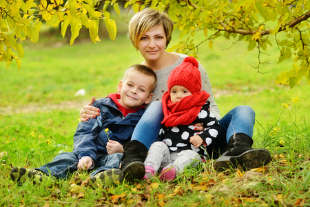 mother with children are sitting on the fall meadow photo