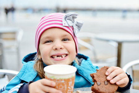 little girl with hot milk and cookie on the street photo