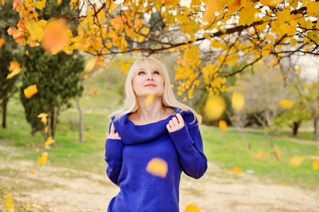 beautiful blonde woman walking outdoors in autumn photo