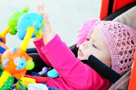 baby carriage: baby in stroller playing toys Stock Photo