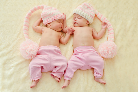 child girl nude: sleeping twins wearing funny hats with big pompoms Stock Photo