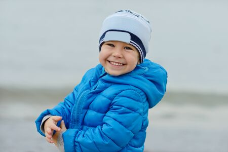 toddler boy: happy toddler boy outdoors wearing blue jacket