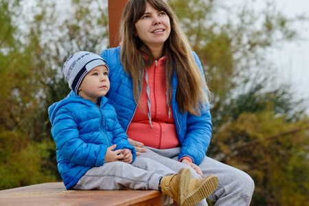 mother on bench: mother and son outdoors are sitting on the bench Stock Photo