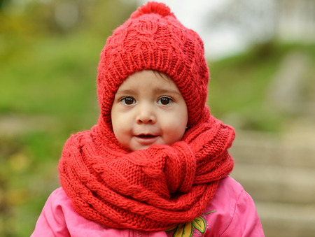 red scarf: toddler girl wearing red scarf and hat  in fall Stock Photo