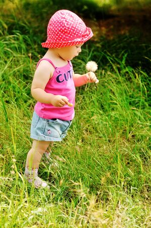 cute baby girl is holding dandelion outdoors photo