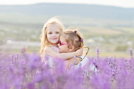 two happy girls are hugging in field photo