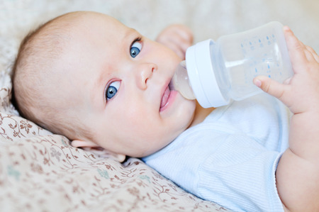 baby holding bottle and drinking water Stock Photo