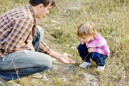 introducing: father introducing toddler daughter to the world of nature and showing little lizard