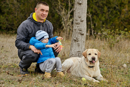 laying forward: father with little son and dog outdoors