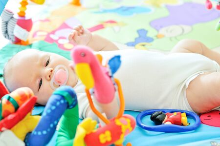 playmat: little baby on the carpet with toys