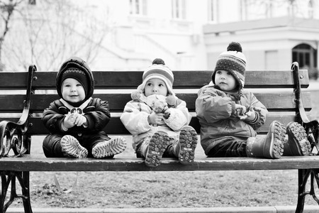 three toddlers are sitting on the bench photo