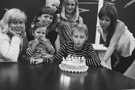 nephew: boy and his family in his birthday in light of candles
