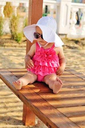 cute summer baby sitting on the beach photo