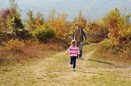 daughter is running to her father in fall forest photo