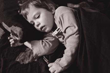 sniffles: toddler girl  is ill and she is laying in the bed