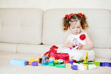 assiduous: toddler girl playing with blocks at home