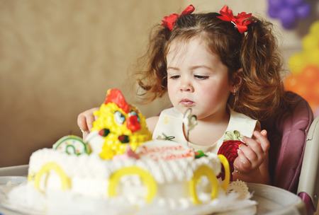 cute toddler girl  with her  birthday  cake photo