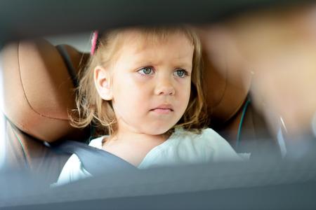 bebe enfermo: niña triste en el asiento del coche Foto de archivo