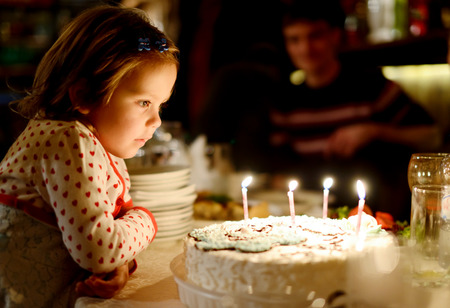 birthday party kids: Little girl blowing out candles in her birthday (shallow focus)